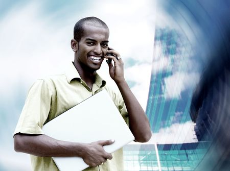 Young happy man or student with laptop and phone on the business background Stock Photo - 7996171