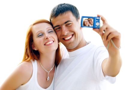 An attractive couple together on the white background, taking a selfportrait.  photo