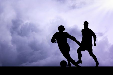 scorching: Silhouettes of footballers on the sunset sky