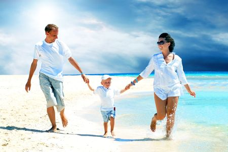 View of happy young family having fun on the beach Stock Photo - 7997236