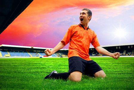 Happiness football player after goal on the field of stadium with blue sky Stock Photo - 7997286