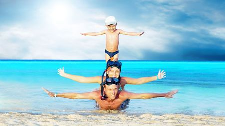 Happy young couple and son with snorkelling on a sea beach Stock Photo - 7997263