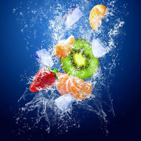 abstract fruit: Gotas de agua alrededor de frutas sobre fondo azul  Foto de archivo