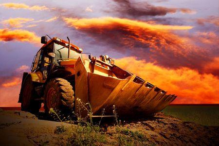 Tracteur jaune sur ciel or surise