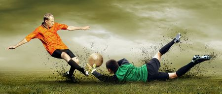 Shoot of football player and goalkeeper on the outdoors field photo