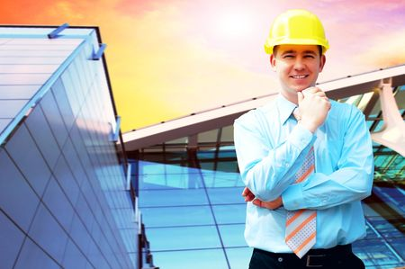 Young architect wearing a protective helmet standing on the building background photo