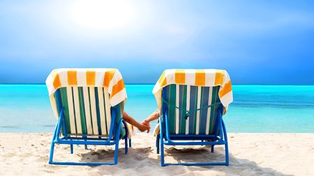 beach chair: Rear view of a couple on a deck chair relaxing on the beach