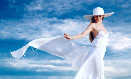 Junge schöne Frauen im weiss mit Pareo auf dem blauen Himmel Hintergrund Standard-Bild