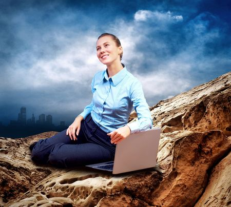 Happy Businesswoman seating with laptop on the mountain under blue sky photo