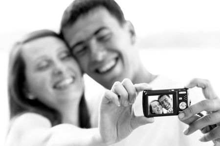 An attractive couple together on the white background, taking a selfportrait. Stock Photo - 8171853