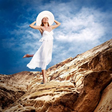 Beautiful girl in White on the mauntain under sky with clouds photo