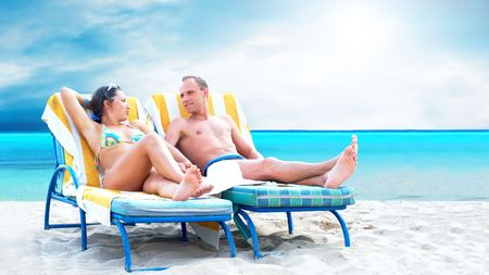 Rear view of a couple on a deck chair relaxing on the beach photo