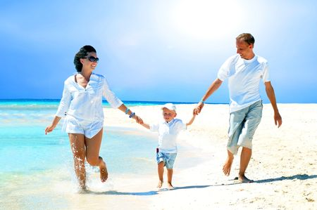 View of happy young family having fun on the beach Stock Photo - 8188662