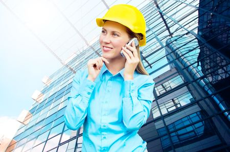 Young architect-woman wearing a protective helmet standing on the building background Stock Photo - 8188666