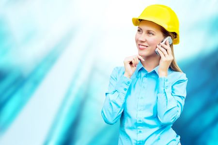 Young architect-woman wearing a protective helmet standing on the building background Stock Photo - 8188559