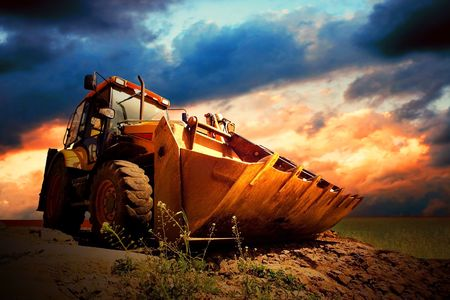 Yellow tractor on golden surise sky