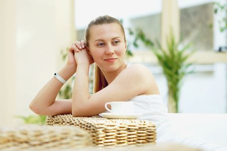 Happy woman in white with cup of coffee or tea at bedroom  photo