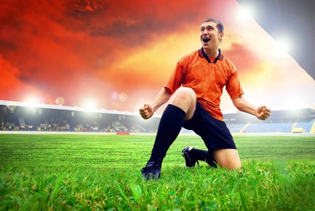 Happiness football player after goal on the field of stadium with blue sky photo