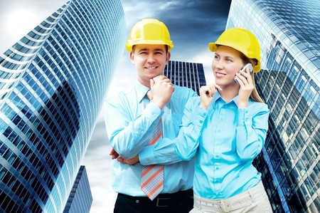 Young architects wearing a protective helmet standing on the building background photo