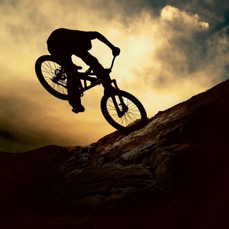moteros: Silueta de un hombre en muontain-bike, sunset