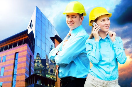 Young architects wearing a protective helmet standing on the building background Stock Photo - 8377621