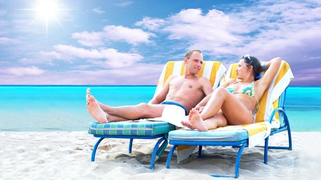 Rear view of a couple on a deck chair relaxing on the beach Stock Photo - 8377619