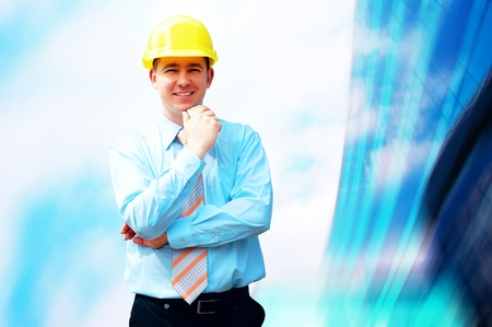 Young architect wearing a protective helmet standing on the building background Stock Photo - 8377608