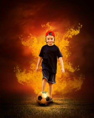 childchood: Child with ball in fires flame on the outdoors field