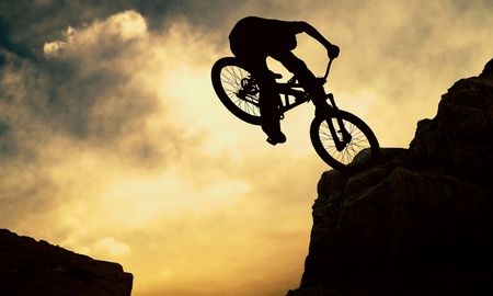 adventure sports: Silhouette of a man on muontain-bike, sunset Stock Photo