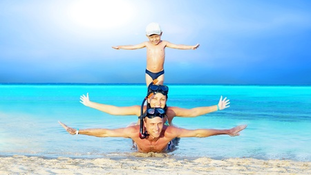 Happy young couple and son with snorkelling on a sea beach photo