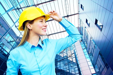 Young architect-woman wearing a protective helmet standing on the building background Stock Photo - 8377931