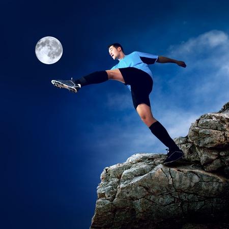 Footballer on the top of mountain at moon night photo