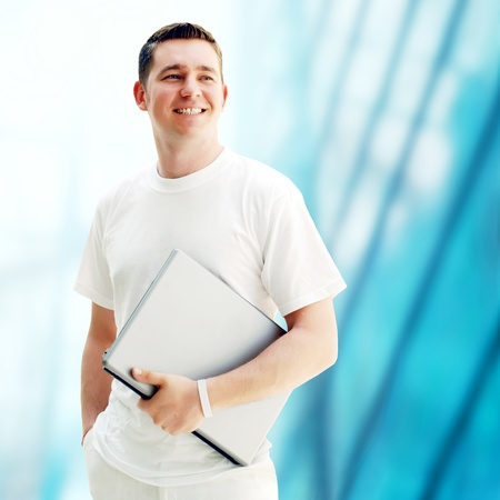 Young happy men or student with laptop on the business background photo