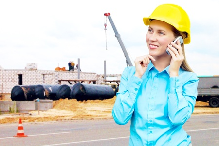 Young architect-woman wearing a protective helmet standing on the building background Stock Photo - 8615895