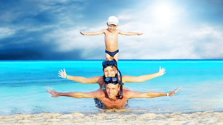 snorkelling: Happy young couple and son with snorkelling on a sea beach Stock Photo