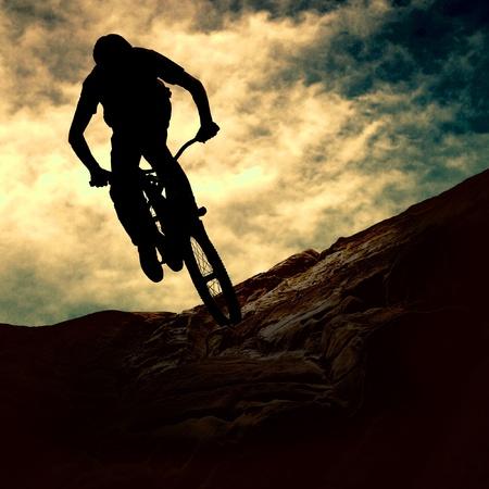 sport bike: Silhouette of a man on muontain-bike, sunset Stock Photo