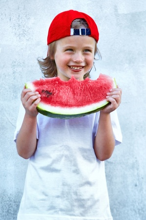 Child with part of watermelon, isolated on the white background photo