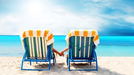 Rear view of a couple on a deck chair relaxing on the beach Stock Photo - 8655346