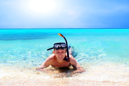 Happy young man with snorkelling on a sea beach photo