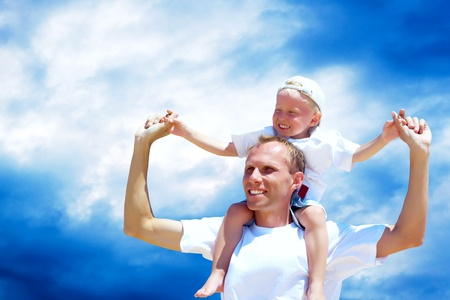 Joyful father giving piggyback ride to his son against a sky background  photo