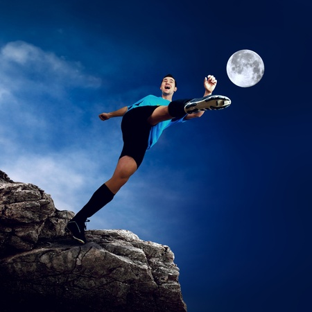 Footballer on the top of mountain at moon night photo