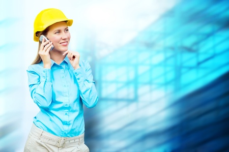 Young architect-woman wearing a protective helmet standing on the building background Stock Photo - 8655619