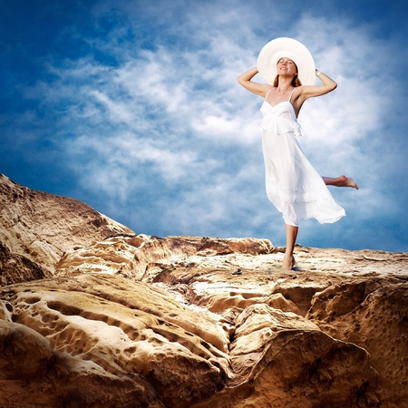 Beautiful girl in White on the mauntain under sky with clouds Stock Photo