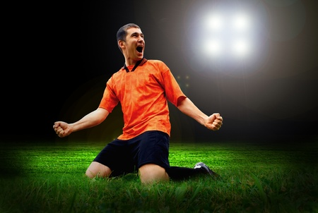 Happiness football player after goal on the field of stadium with light photo
