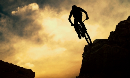 Silhouette of a man on muontain-bike, sunset photo