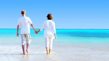 esposas: Vista posterior de una pareja caminando en la playa, manos.