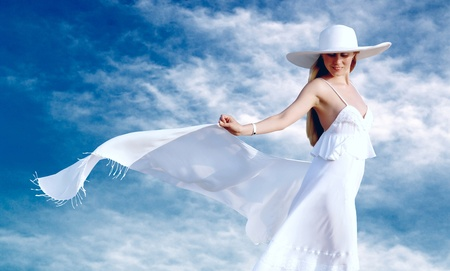 Young beautiful women in the white with pareo on the blue sky background photo