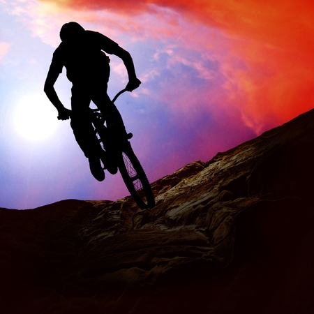 bikers: Silhouette of a man on muontain-bike, sunset Stock Photo