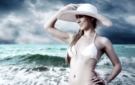Young beautiful women on the sunny tropical beach in bikini and white hat photo
