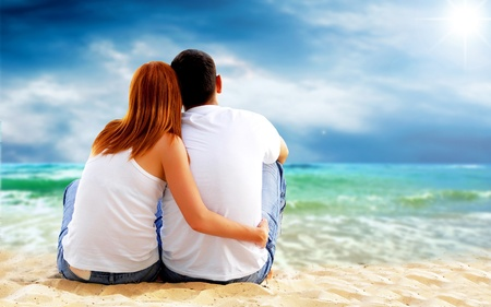 femme romantique: Vue sur la mer d'un couple assis sur la plage.